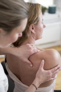 Bilde av kiropraktor Hege Nielman som undersøker en pasient sin skulder